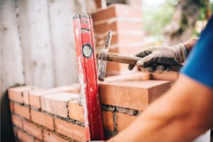Brick Masonry performed by worker with a hammer and a leveler
